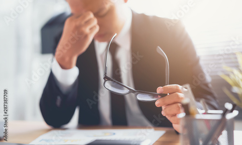 Fotografia  Businessman in black suit of hands touching on the eyes due to tiredness from working computer for a long time, may be the cause of office syndrome
