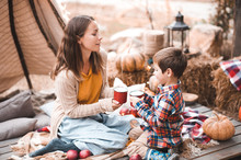 Mother With Kid Boy Drinking Hot Chocolate Outdoors At Autumn Season. Woman With Child Having Picnic Over Pumpkins. Thanksgiven Day.