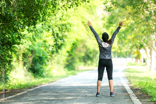 Healthy smiling woman warming up stretching her arms and looking away in the road outdoor Fototapete