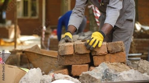 Blue collar worker stacking bricks at construction site.