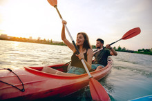 Confident Young Caucasian Couple Kayaking On River Together With Sunset In The Backgrounds. Having Fun In Leisure Activity. Romantic And Happy Woman And Man On The Kayak. Sport, Relations Concept.