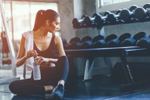 Fit Young Woman Sitting And Resting After Workout Or Exercise In Fitness Gym. Woman At Gym Taking A Break And Relax With Water In Sportswear. Fitness Concept, Healthy, Sport, Lifestyle