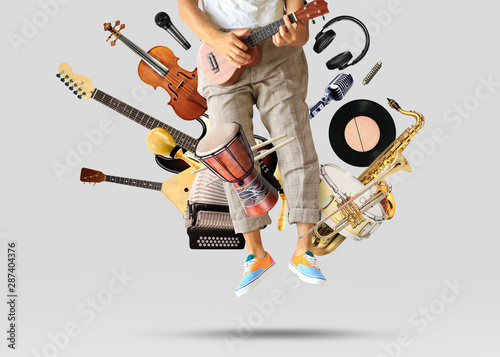 Fototapeta Young man sits and plays guitar among musical instruments