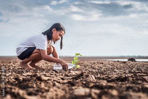 Obraz na plátně  Asian girl watering green plant in dry land,Crack dried soil in drought and ,Climate change from global warming