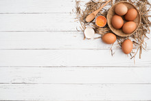 Top View Brown Chicken Egg  In Bamboo Basket And Egg Yolk On The Hay With White Wooden Table Background, Flat Lay With Copy Space