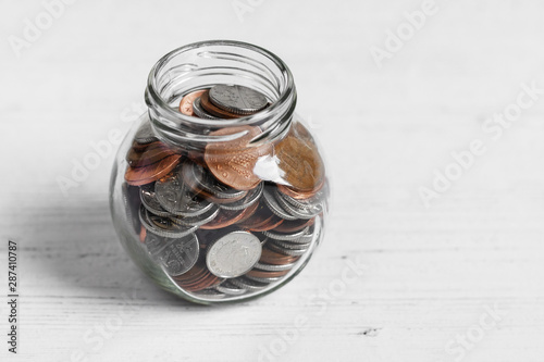 Pinturas sobre lienzo  Coin jar on a white table top, money savings concept with copy space