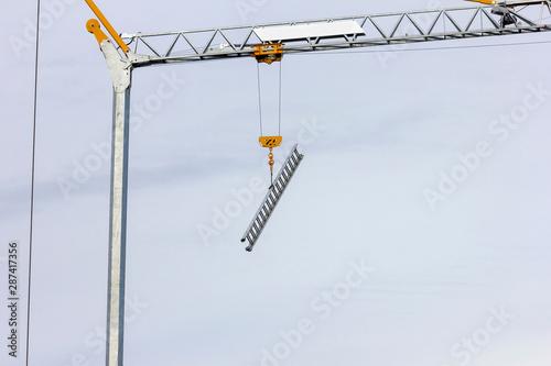 A portrait of a ladder hanging on a crane's grapling hook so it would not get stolen Canvas Print