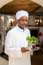 An Egyptian Man Holds A Tray With A Glass Of Mint Tea And Some Fresh Mint Leaves, Aswan, Egypt