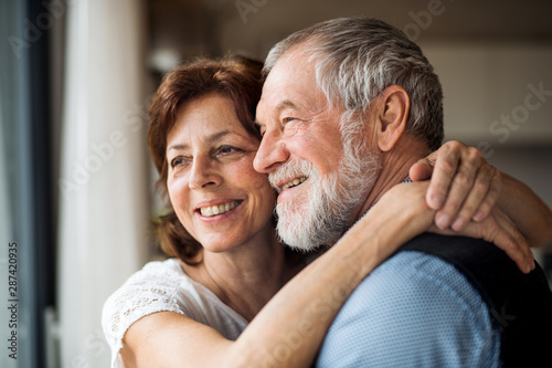 A senior couple indoors at home, looking out of window. Tableau sur Toile