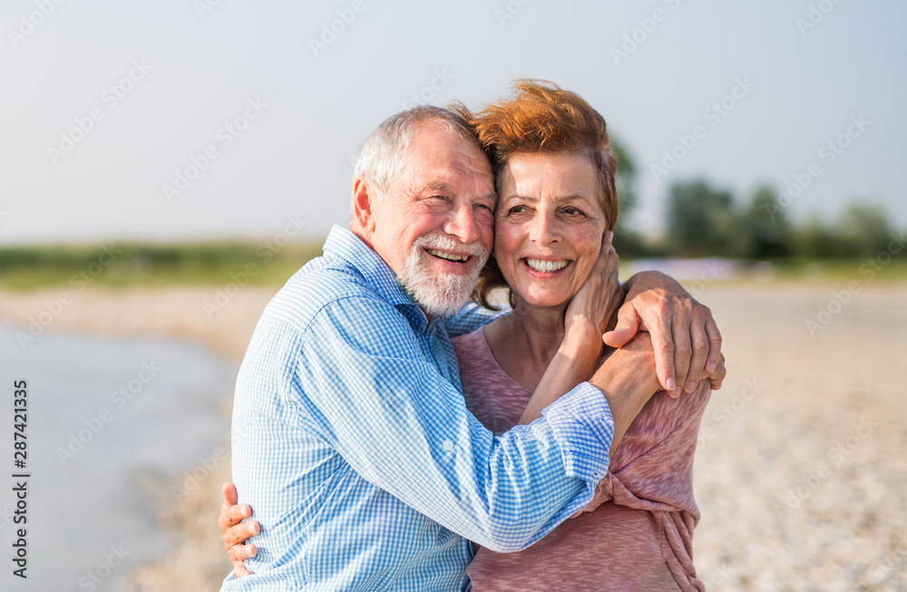 Fototapeta Senior couple on a holiday on a walk by the lake, hugging.