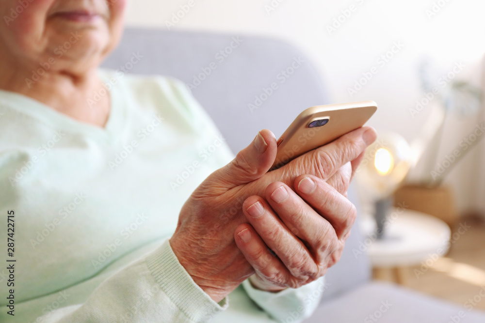 Fototapety, obrazy: Elderly woman holding blank screen cell phone gadget in hands. Old lady with wrinkled skin trying to vigure out touchscreen smartphone. Background, close up, overhead, top view, copy space.