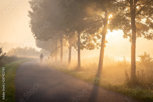 Fototapeten Natur Cyclist in the fog on the towpath along the Lys in Lauwe - Menen, Belgium. After a cold and clear night we often get a layer of fog over the fields. This creates beautiful atmospheric pictures of the