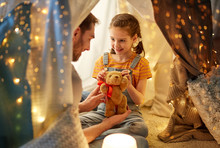 Family, Hygge And People Concept - Happy Father With Teddy Bear Toy And Little Daughter Playing In Kids Tent At Night At Home