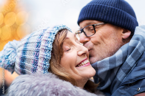 Foto auf Gartenposter Individuell love, christmas and people concept - close up of happy senior couple kissing outdoors in winter