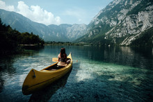 Young Woman Canoeing In The Lake Bohinj On A Summer Day, Background Alps Mountains.