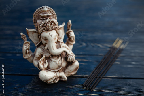 Obraz na plátně  Hindu god Ganesh on black background. Statue on wooden table