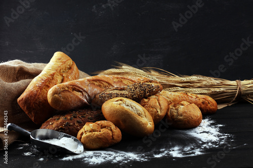 Fotografie, Obraz Assortment of baked bread and bread rolls on black table background