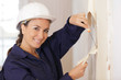 canvas print picture - woman plasterer mixing the filler
