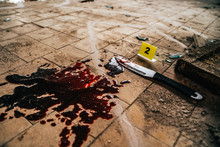 Crime Scene With Knife Marked With Number In Blood Of Victim On Floor. Investigation Of Cruel Murder Concept