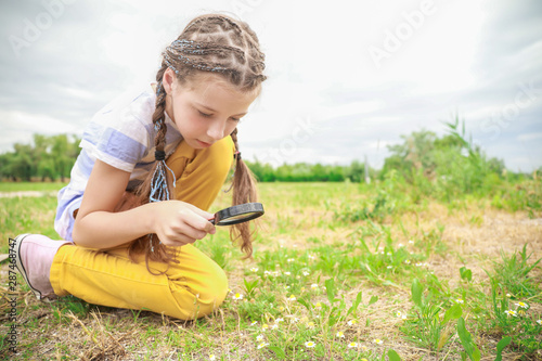 Little girl with magnifying glass studying nature outdoors Fototapeta