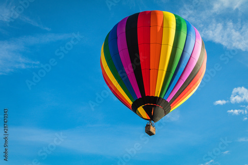 Poster Montgolfière / Dirigeable Rainbow colorful hot-air balloon floats on a summer morning with bright blue sky