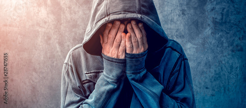 Fotografía Desperate man in hooded jacket is crying