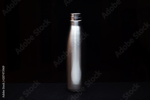 Close-up of steel thermo bottle on black. Canvas Print