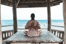 Young Woman Doing Yoga In The Wooden Gazebo At The Beach