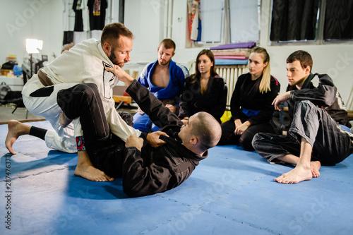 Fototapeta  Brazilian Jiu JItsu BJJ professor teaching technique from the guard position to