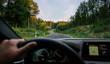 Leinwanddruck Bild - hands of car driver on steering wheel, road trip, driving on highway road