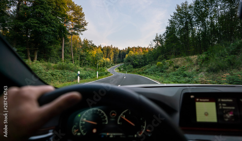 Türaufkleber Natur hands of car driver on steering wheel, road trip, driving on highway road