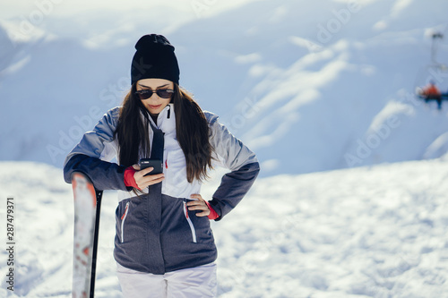 Fototapeta young and active brunette skiing in the snowy mountains obraz