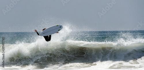 A Surfer jumps a big Wave At Newport Beach In California