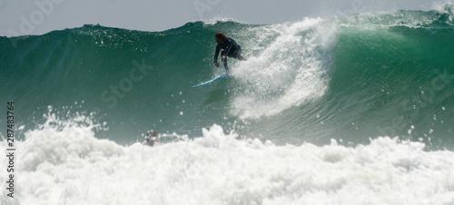 A Surfer rides a big Wave At Newport Beach In California