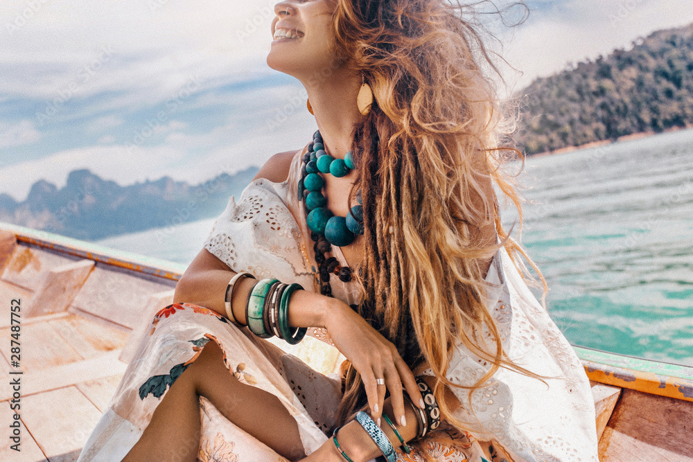 Fototapeta close up of fashionable young model in boho style dress on boat at the lake
