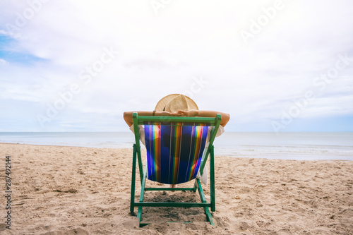 A woman lying down on a beach chair with feeling relaxed Wallpaper Mural