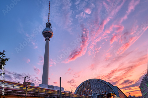 Local train with motion blur and the famous Television Tower in Berlin at sunset Wallpaper Mural