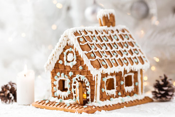 Homemade gingerbread house on a light background with bokeh, selective focus