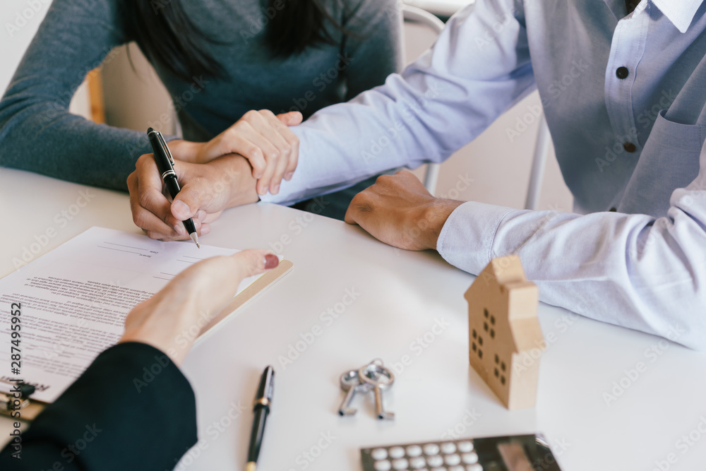Fototapeta Salesmen are letting the male customers sign the sales contract house, Asian women and couple are doing business in the office , Business concept and contract signing
