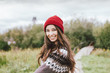 Beautiful carefree long hair asian girl in the red hat and knitted nordic sweater in autumn nature park