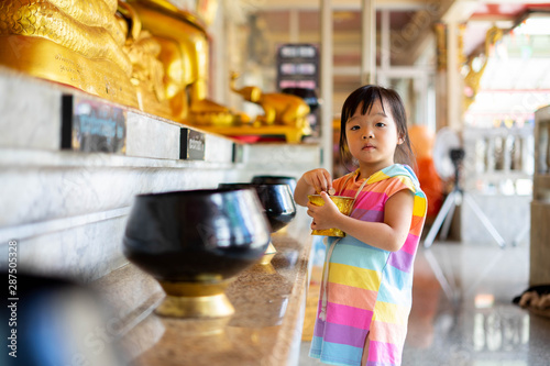 Little girl putting coins in one of monk alms bowl for merit in buddhism with lots of monk alms bowls beside in a temple Wallpaper Mural