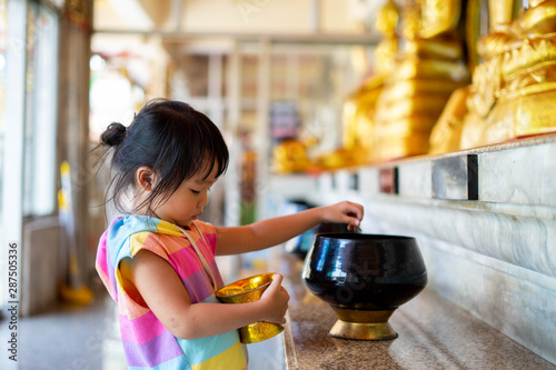 Photo Little girl putting coins in one of monk alms bowl for merit in buddhism with lots of monk alms bowls beside in a temple