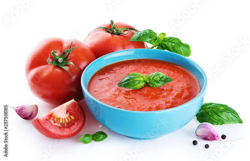 Bowl of tomato soup, tomatoes, garlic and basil  isolated on a white background.