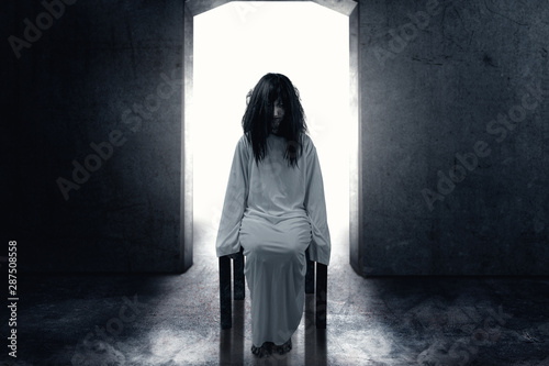 Fotografía  Scary ghost woman with blood and dirty face sitting in the dark room