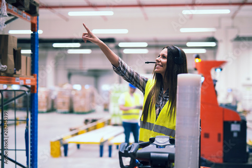 Cuadros en Lienzo  Female forklift operator with headset communication equipment showing location on the shelf to place packages in large warehouse storage center while worker organizing distribution in background