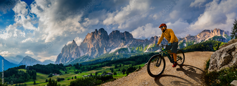 Fototapety, obrazy: Man cycling on electric bike, rides mountain trail. Man riding on bike in Dolomites mountains landscape. Cycling e-mtb enduro trail track. Outdoor sport activity.