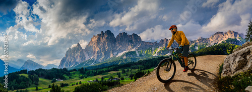 Man cycling on electric bike, rides mountain trail. Man riding on bike in Dolomites mountains landscape. Cycling e-mtb enduro trail track. Outdoor sport activity.