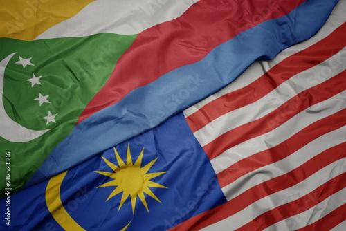 Photo waving colorful flag of malaysia and national flag of comoros.