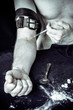 The man's hand is tied with a belt. The syringe with the needle is close to the vein.
