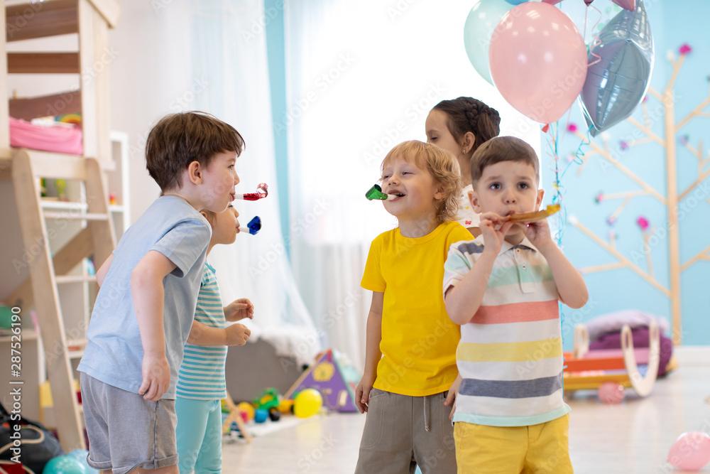 Fototapeta Children birthday party. Kids play and blow noisemaker horns
